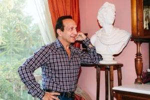 Ο Σπύρος Μπιμπίλας σε φωτογραφία μπροστά από ένα άγαλμα